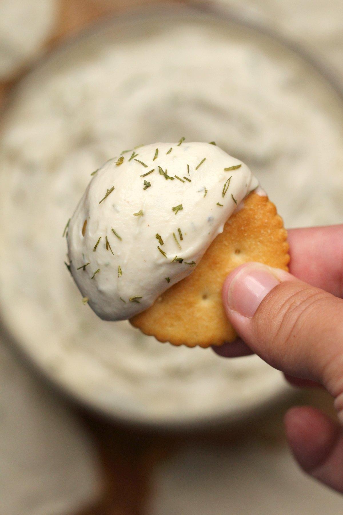 A cracker with vegan cream cheese.