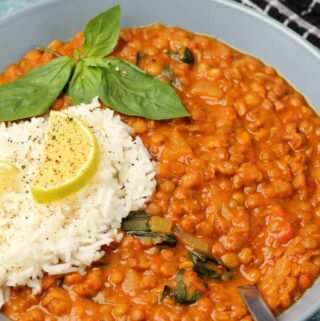 Vegan lentil curry with rice in a blue bowl.