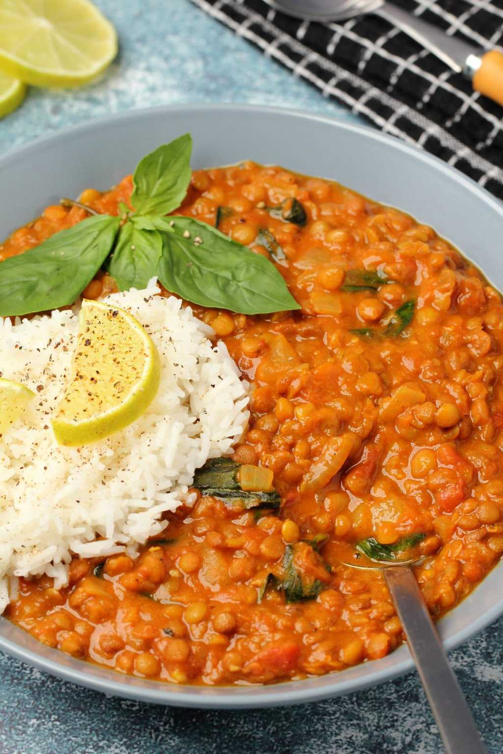 Vegan lentil curry with basmati rice and fresh basil in a blue bowl.