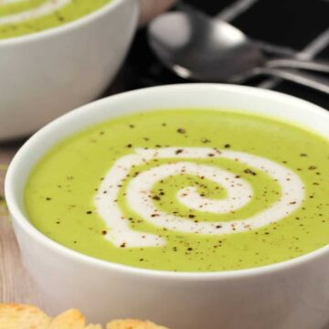 Vegan pea soup topped with a swirl of vegan cream in white bowls.