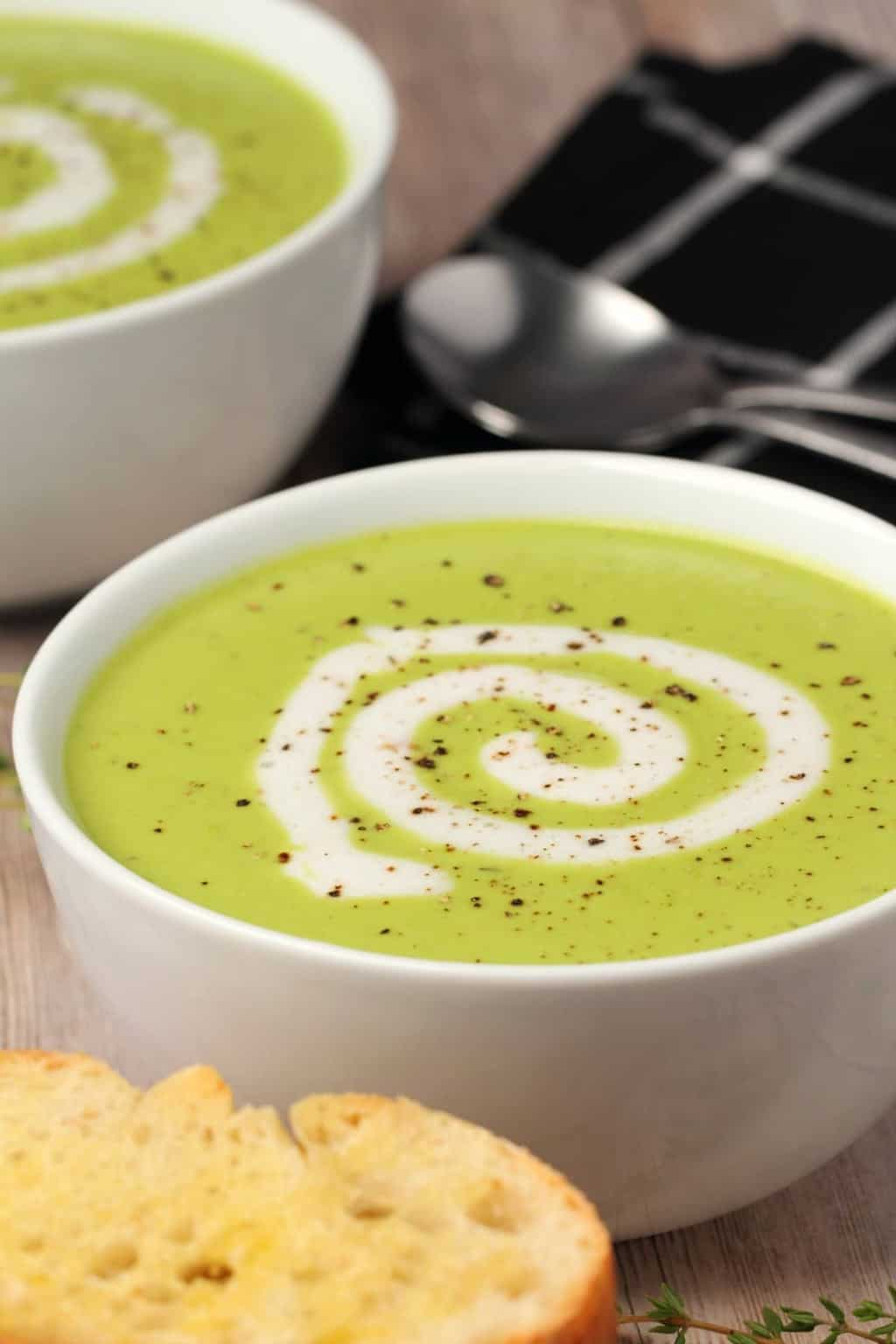 Vegan pea soup topped with a swirl of coconut cream and a sprinkle of black pepper in a white bowl.