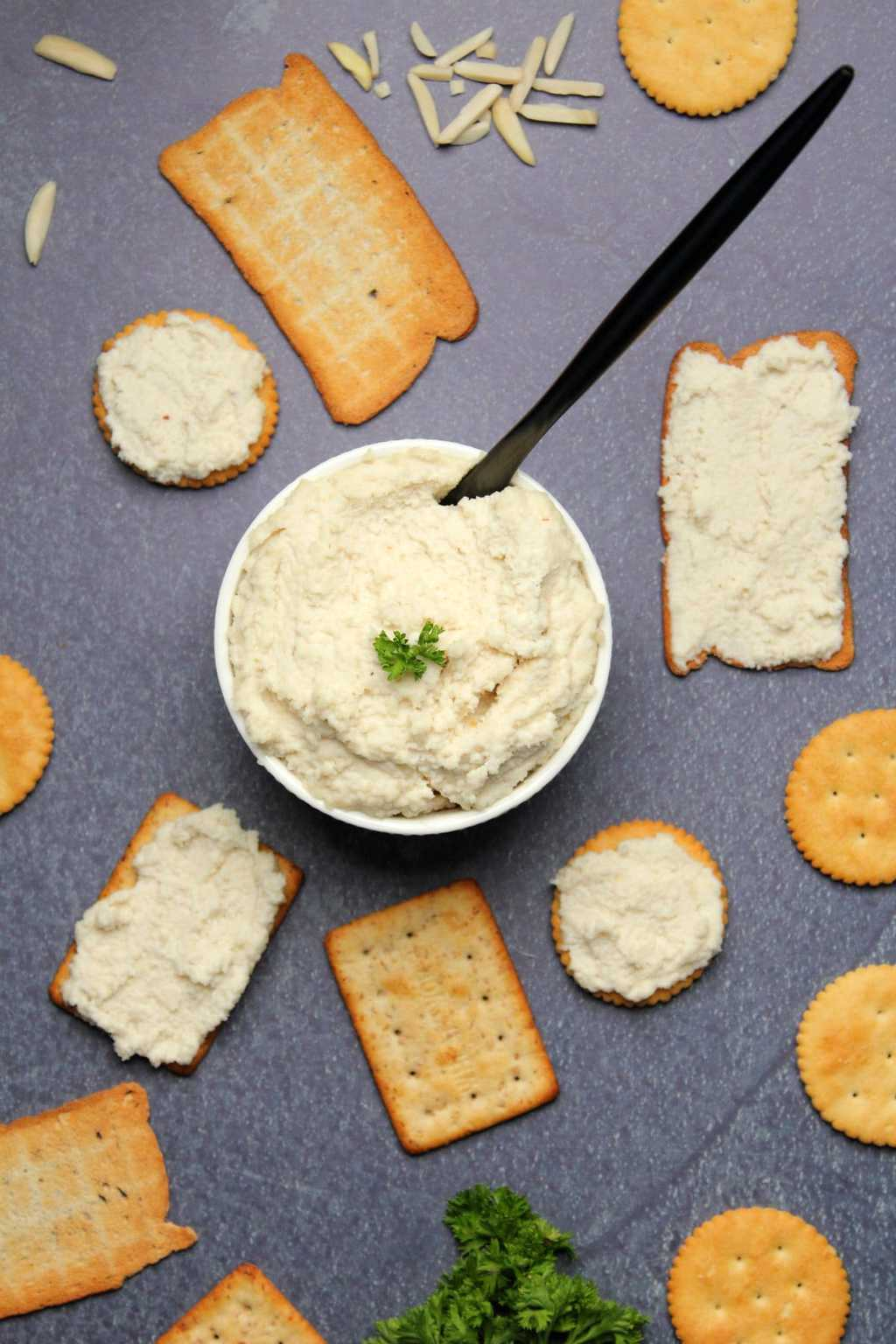 Vegan ricotta in a white bowl surrounded by crackers.