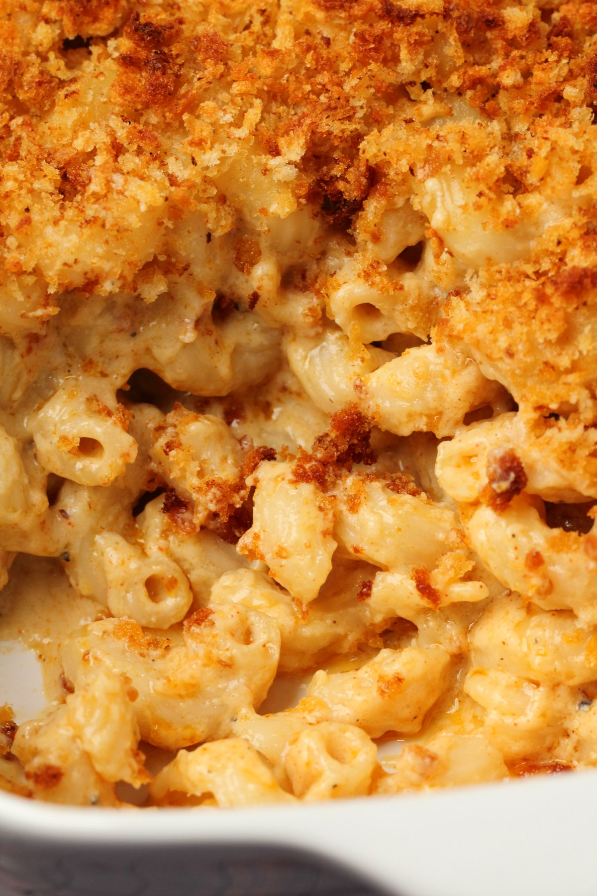 Baked vegan mac and cheese in a white dish.