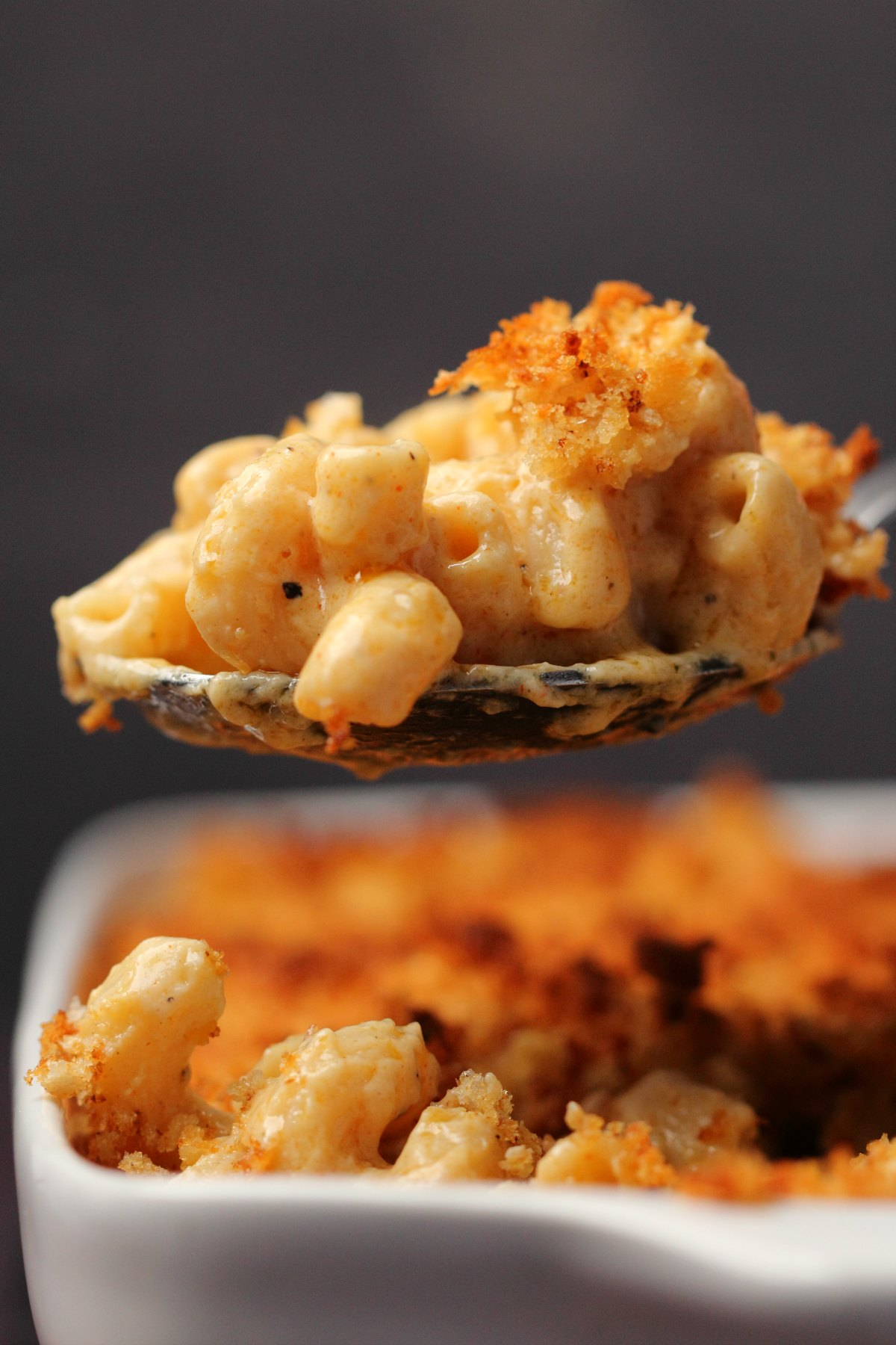 A large spoonful of vegan mac and cheese lifting out of a white dish.