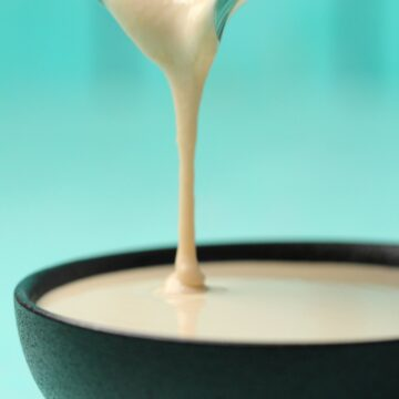 Tahini sauce pouring from a glass jug into a black bowl.