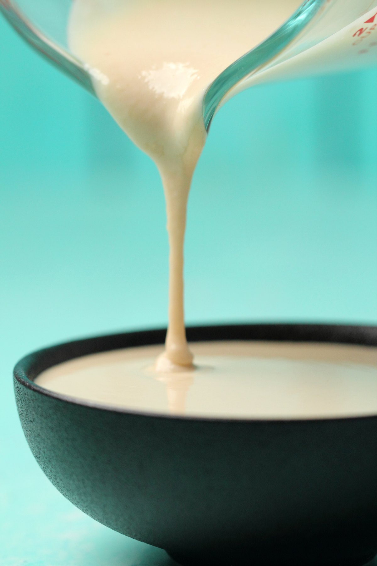 Tahini sauce pouring from a jug into a round black dish.
