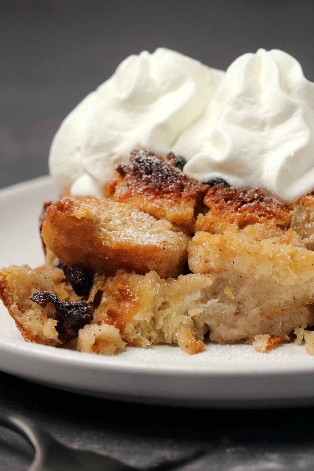 Vegan bread pudding topped with vegan cream on a white plate.