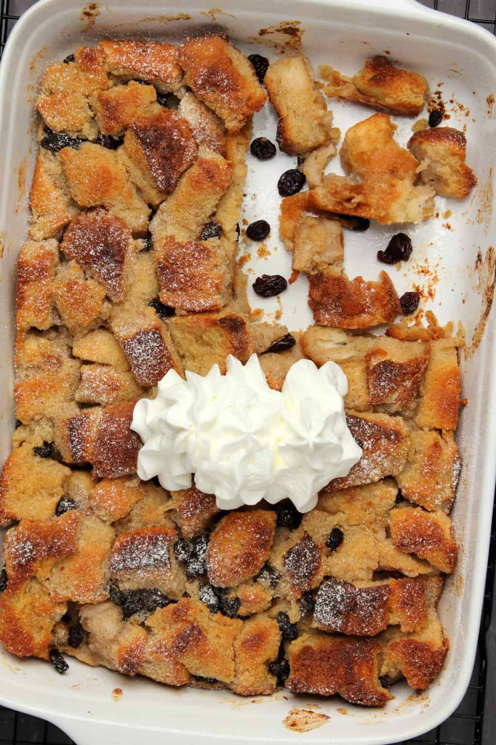 Vegan bread pudding topped with vegan cream in a white baking dish.