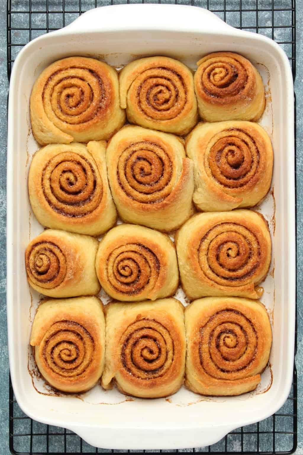 Vegan cinnamon rolls fresh from the oven in a white baking dish.
