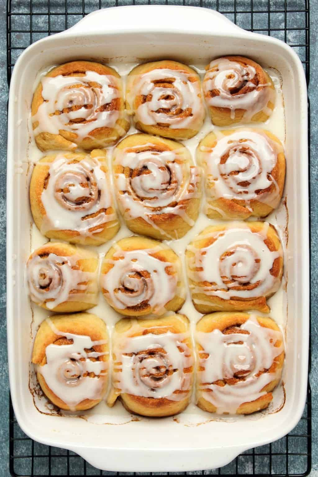 Vegan cinnamon rolls topped with frosting in a white baking dish.