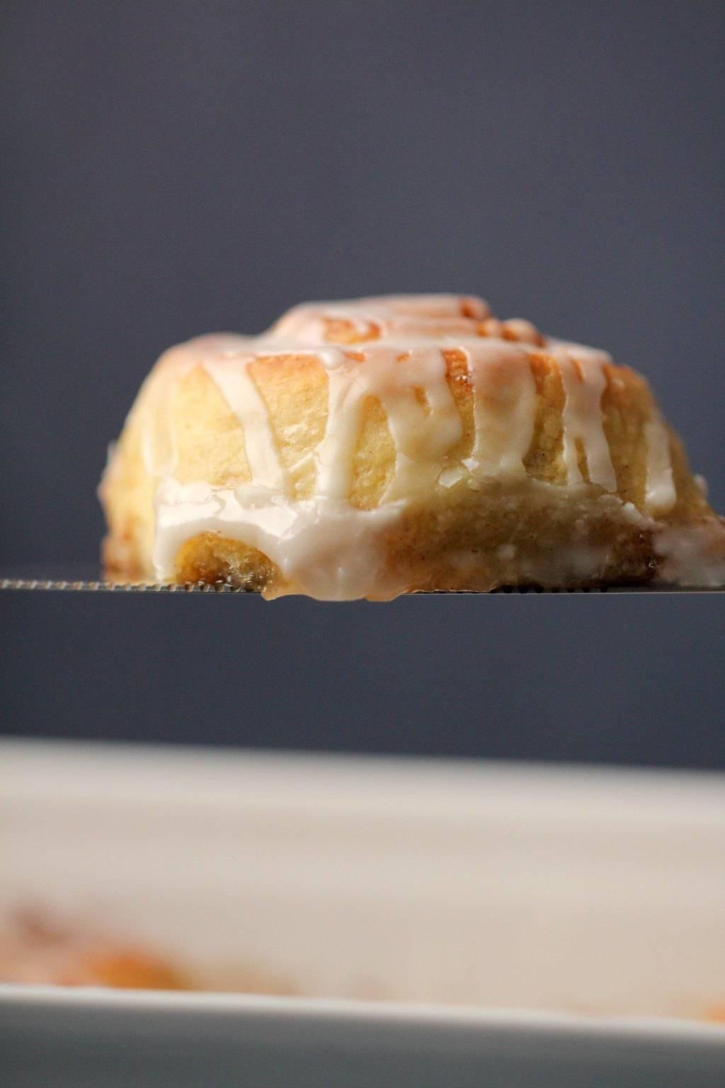 Vegan cinnamon roll on a silver cake lifter.