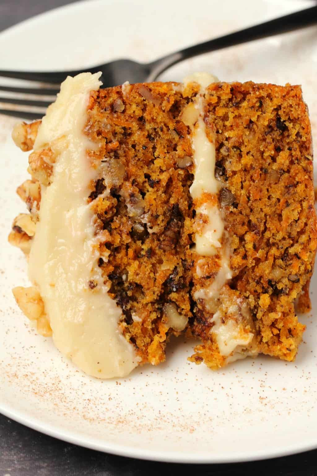 Slice of vegan carrot cake with vegan cream cheese frosting on a white plate.