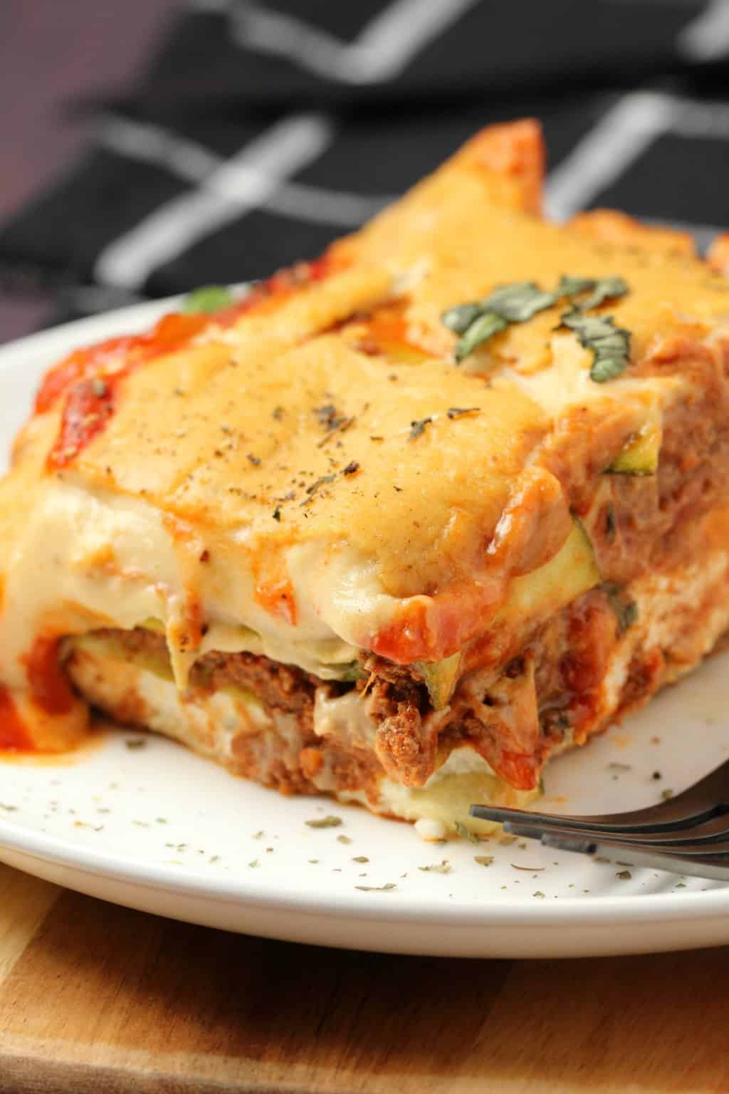 A slice of vegan lasagna on a white plate with a fork.