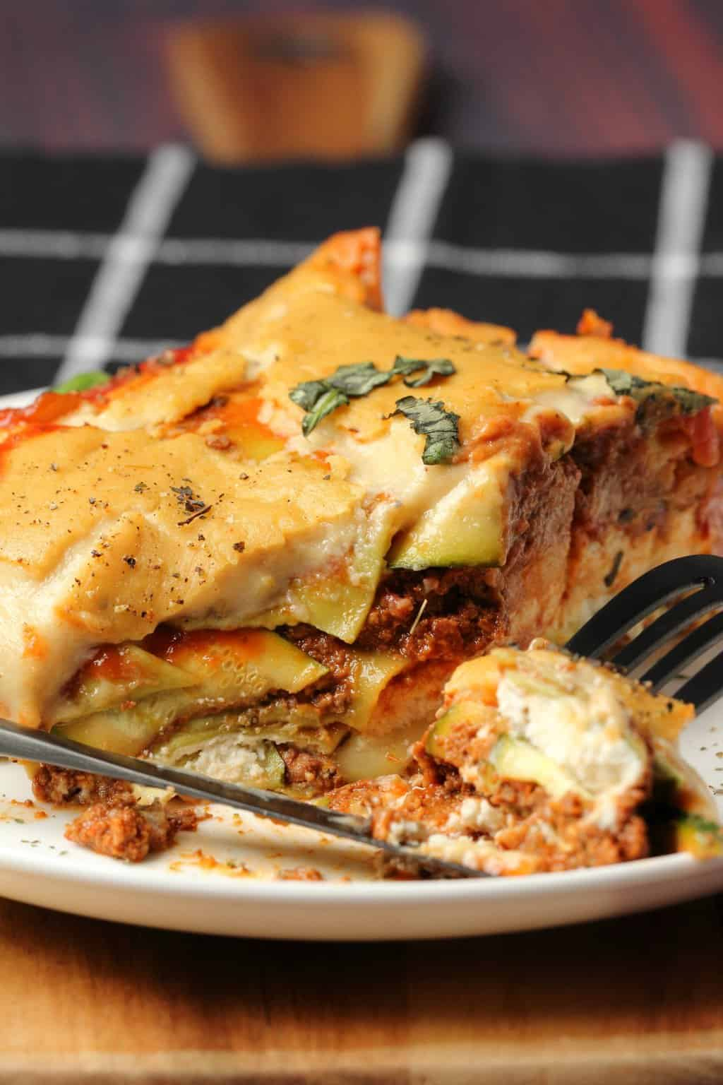 Slice of vegan lasagna on a white plate with a fork.