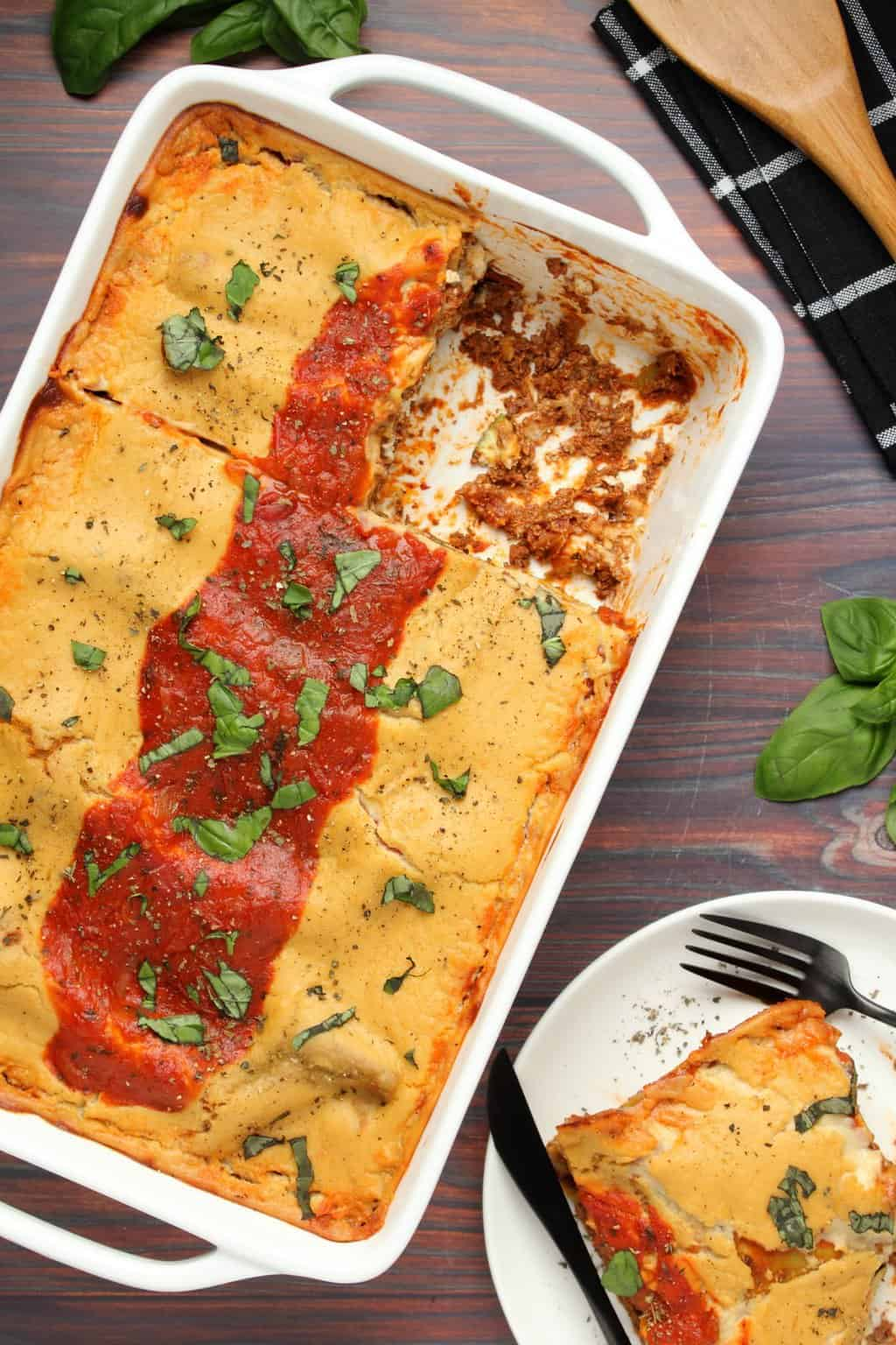 Vegan lasagna in a white dish with one slice removed.