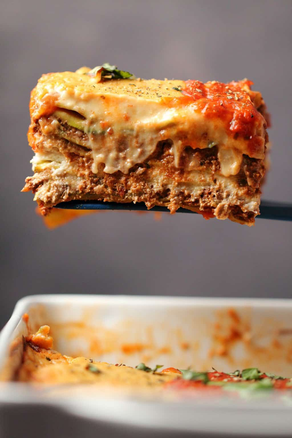 A slice of vegan lasagna lifting out of a white dish.