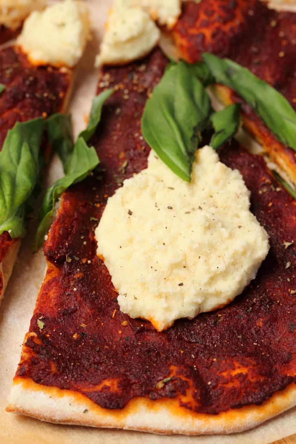 Vegan pizza topped with fresh basil and vegan ricotta.