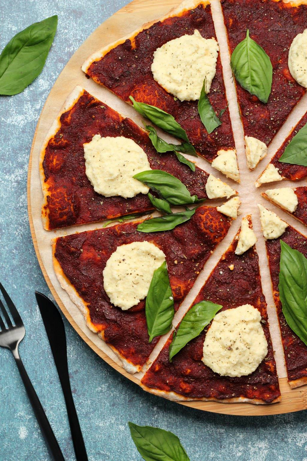 Vegan pizza topped with vegan ricotta and fresh basil leaves.