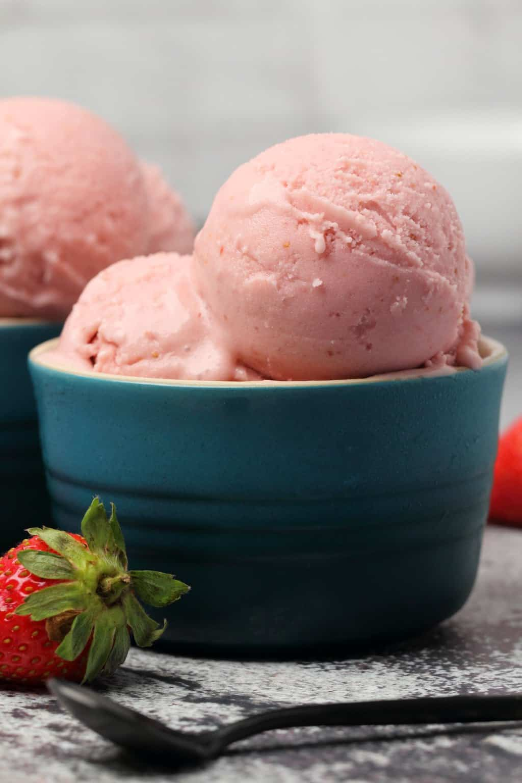 Vegan strawberry ice cream scoops in bowls.