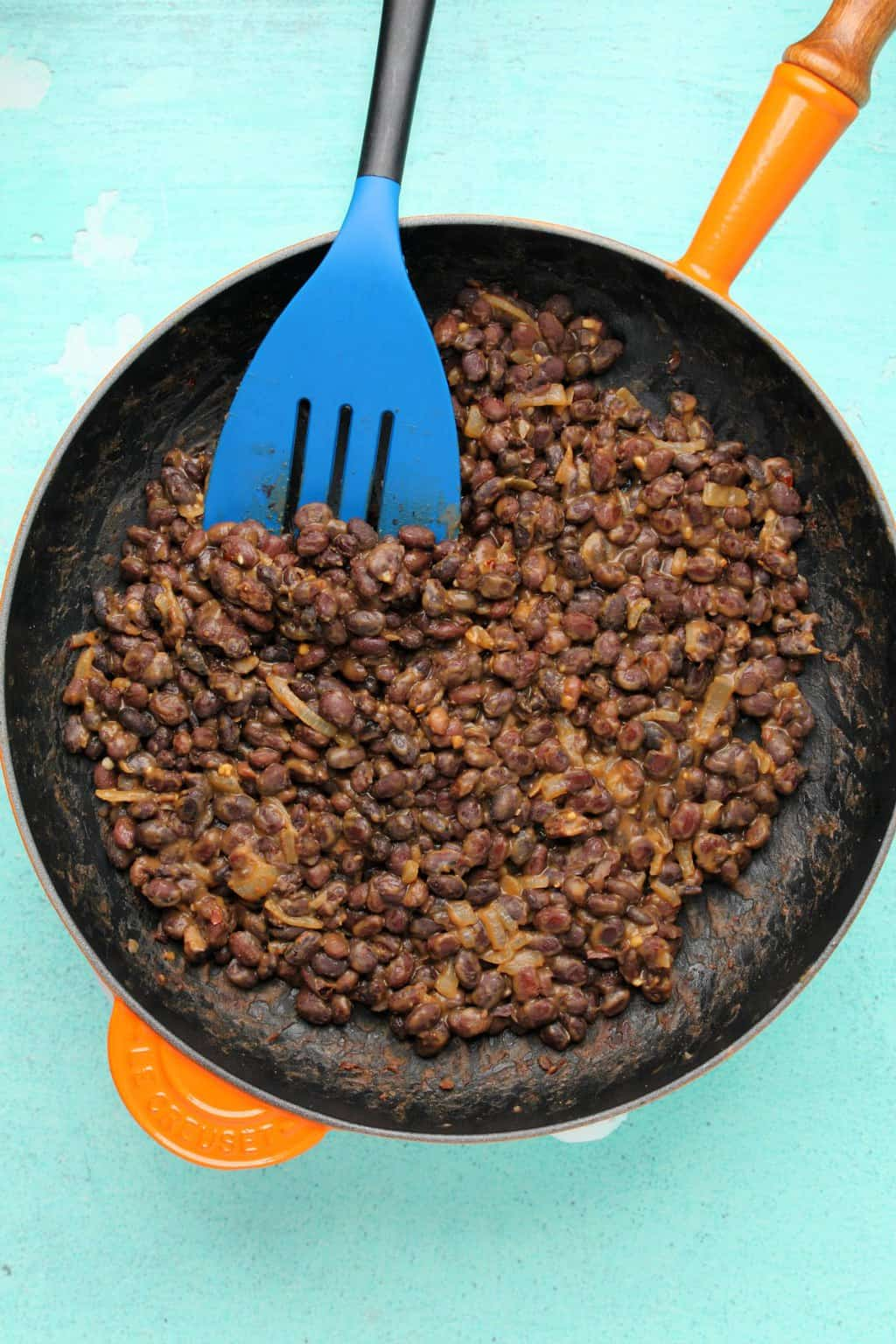 Black beans for vegan tacos, with onions and spices mixed up in a frying pan.
