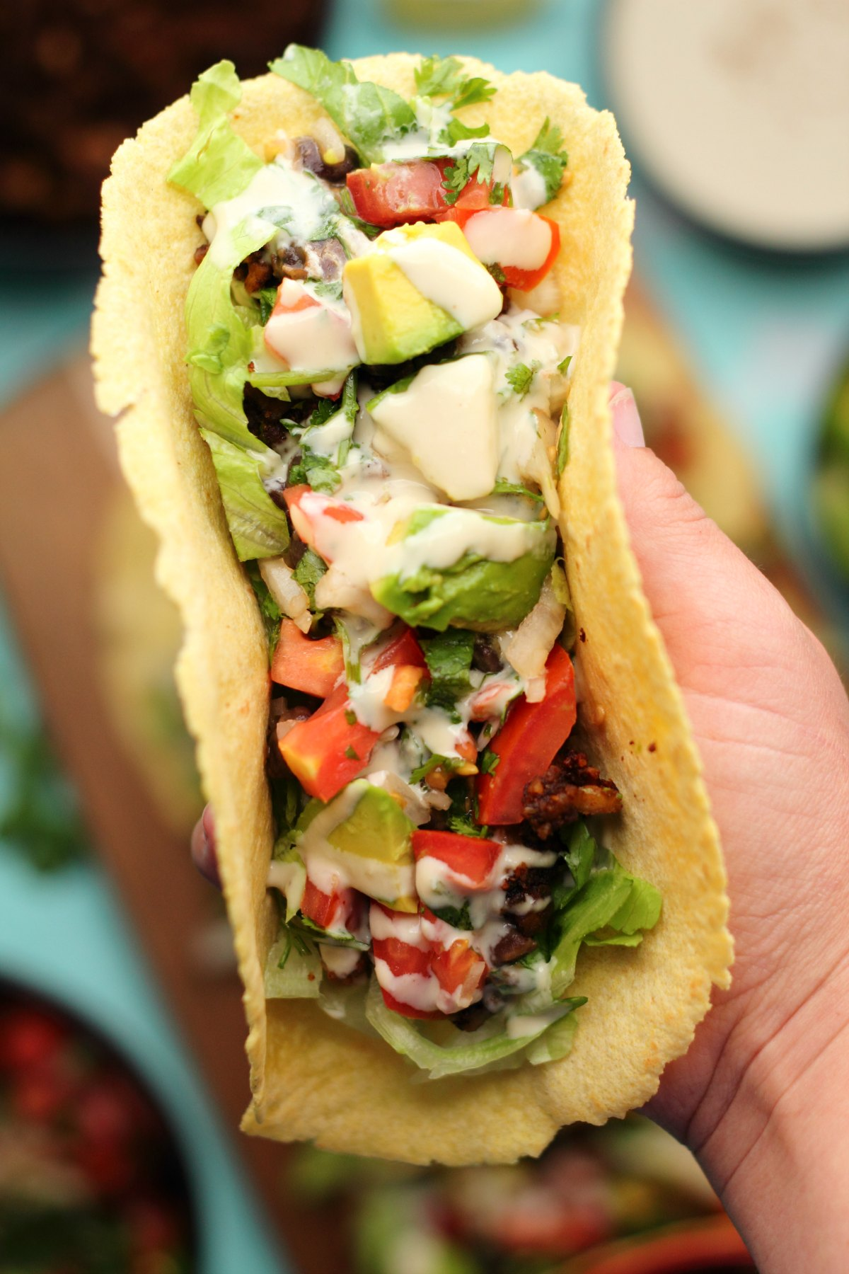 Vegan taco stuffed with black beans, vegan taco meat, pico de gallo, avocado and tahini sauce.