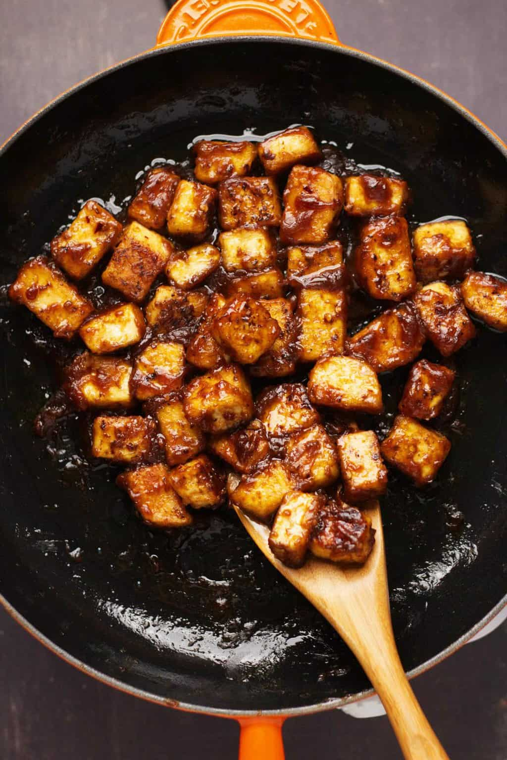 General Tso's tofu in a frying pan with a wooden spoon.
