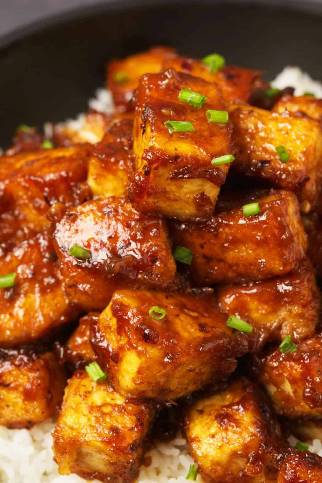 General Tso's tofu served with basmati rice and chopped chives in a black bowl.