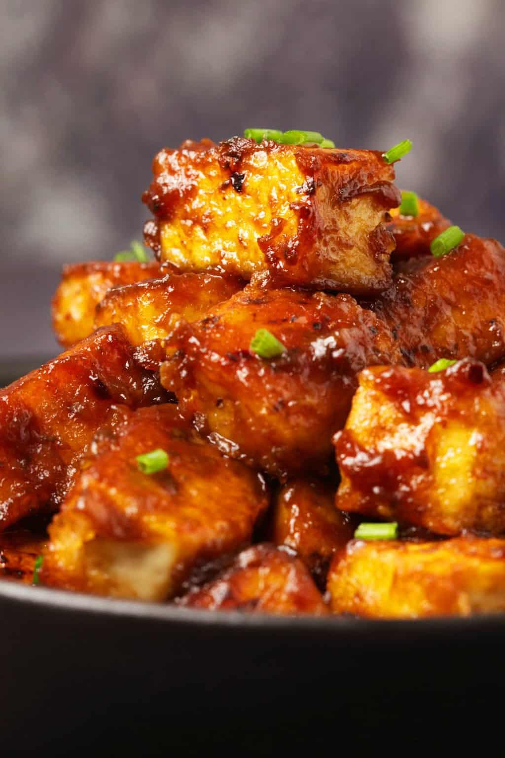 General Tso's tofu topped with chopped chives in a black bowl.