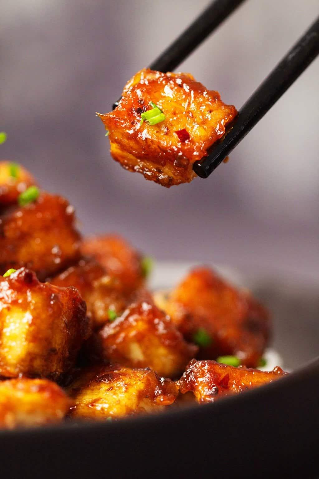 General Tso's tofu in a black bowl with chopsticks.