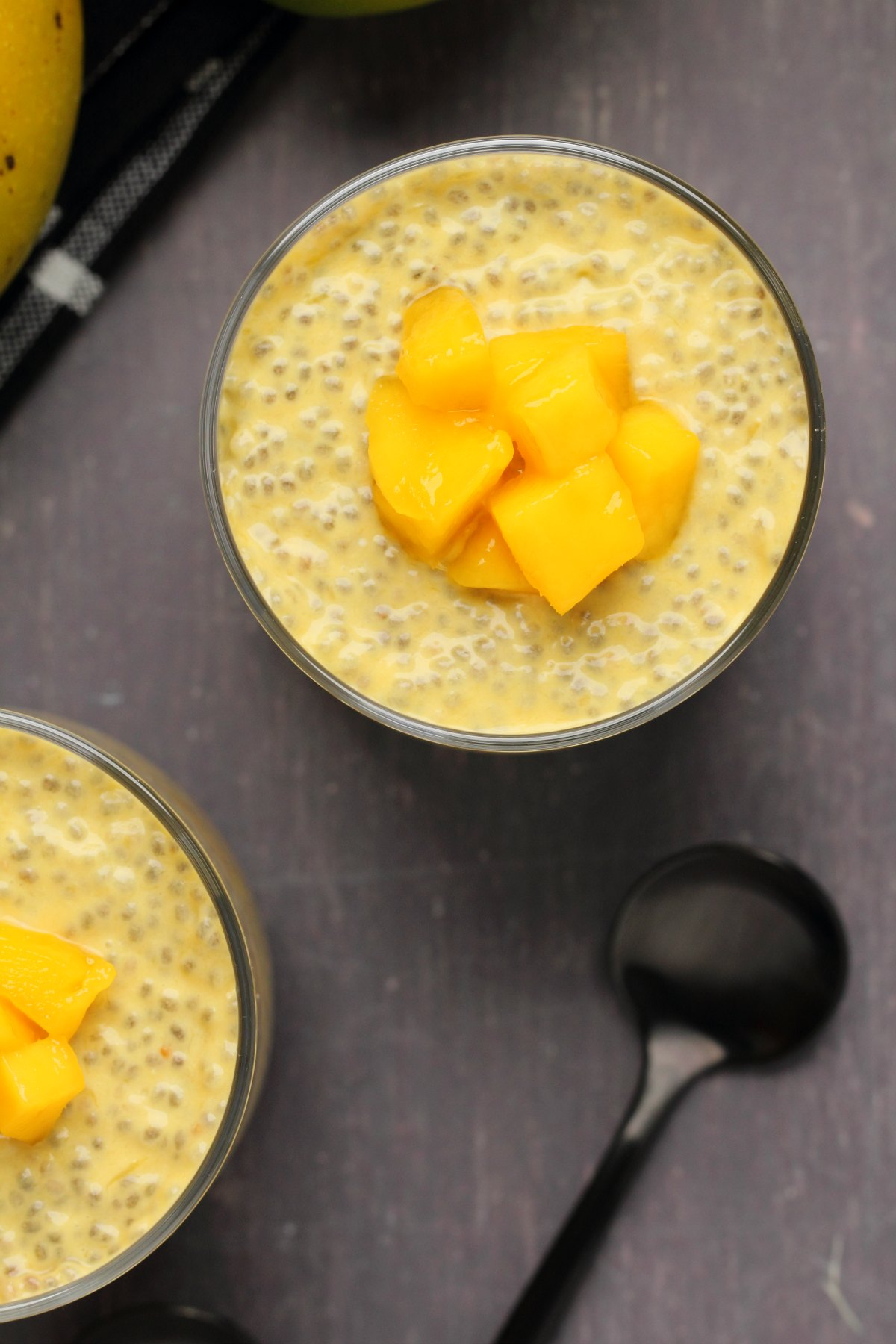 Mango chia pudding topped with mango chunks in glasses.
