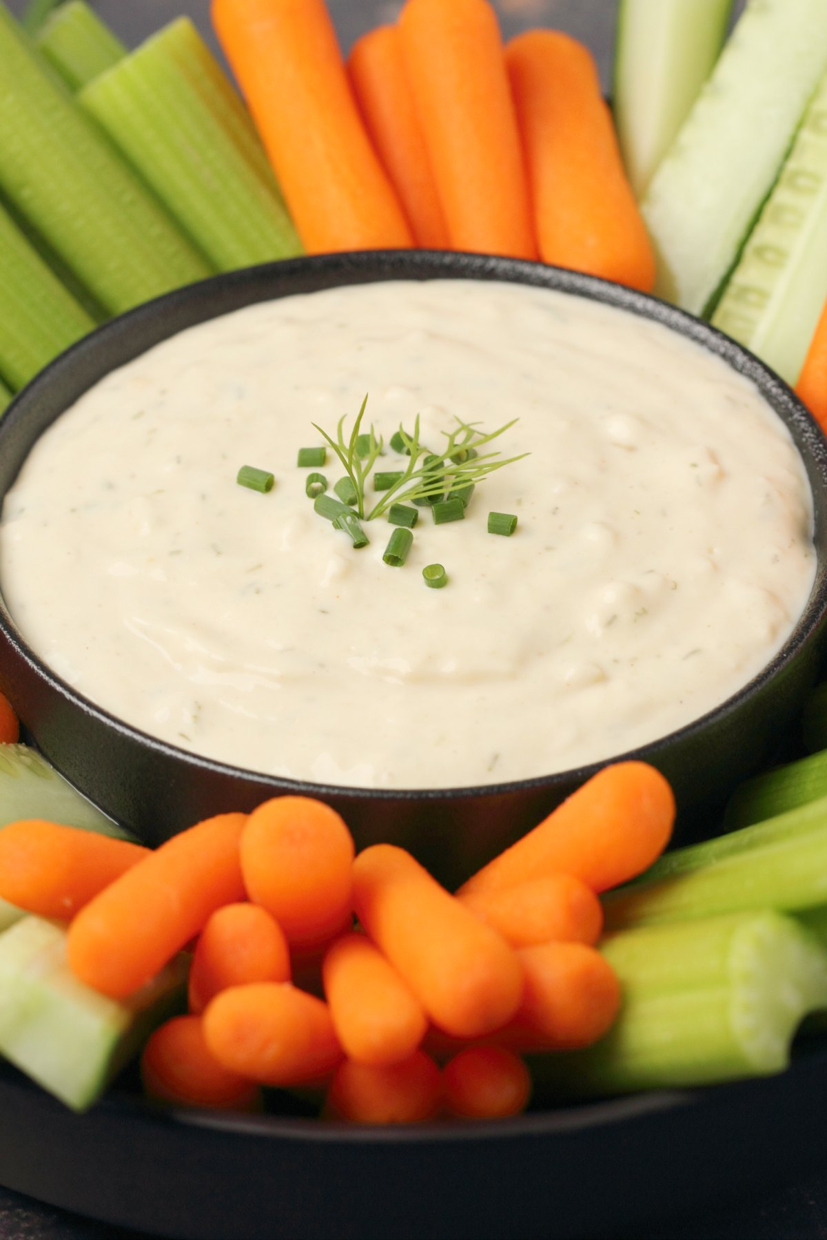 Vegan blue cheese dressing topped with chopped chives in a black bowl.
