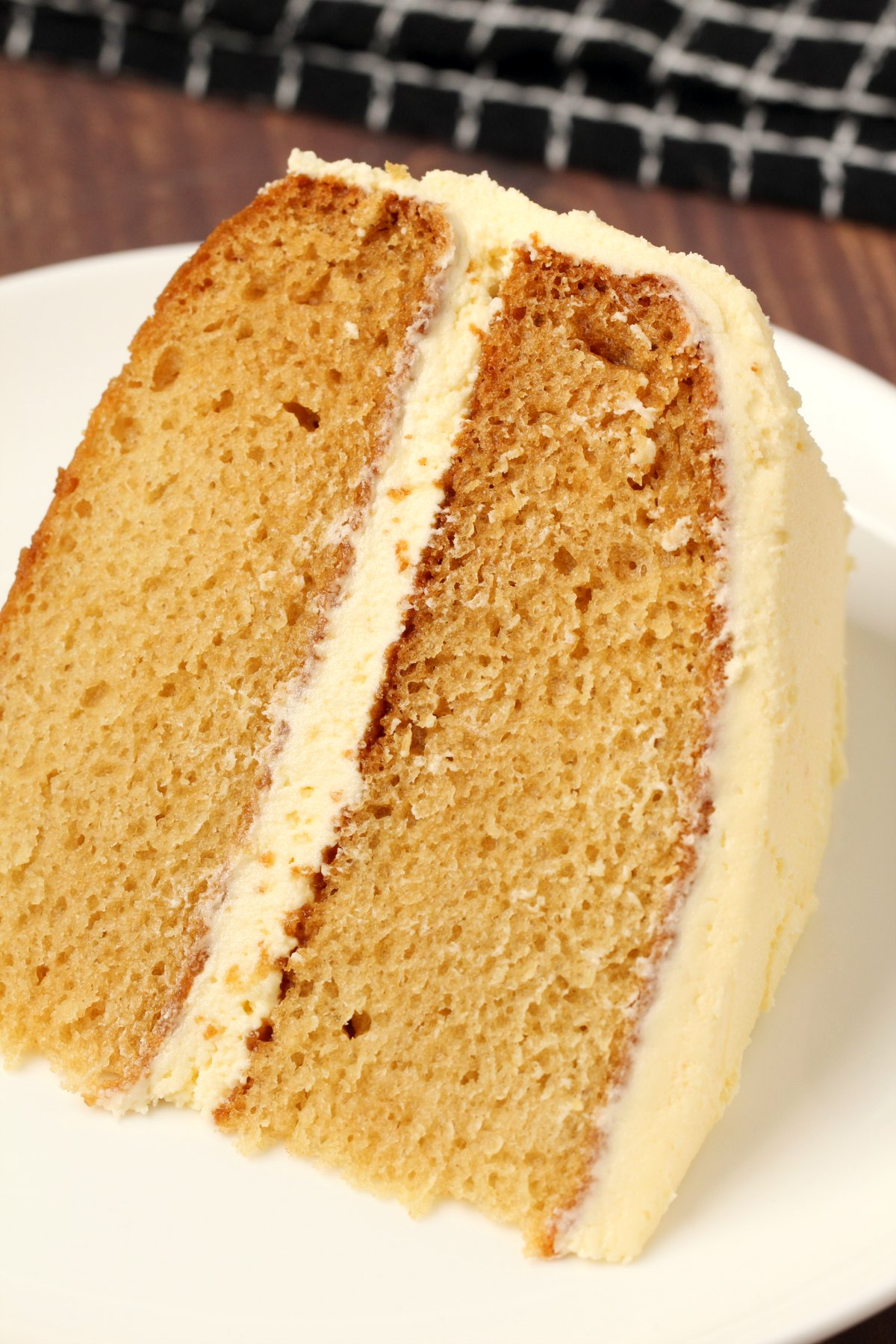 A slice of vegan vanilla cake on a white plate.