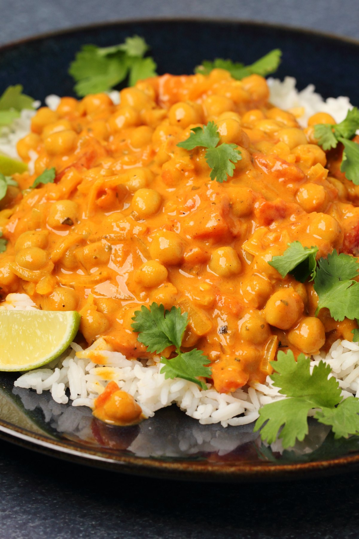 Chickpea curry served over basmati rice in a black bowl.