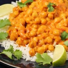 Vegan chickpea curry with rice in a black bowl.