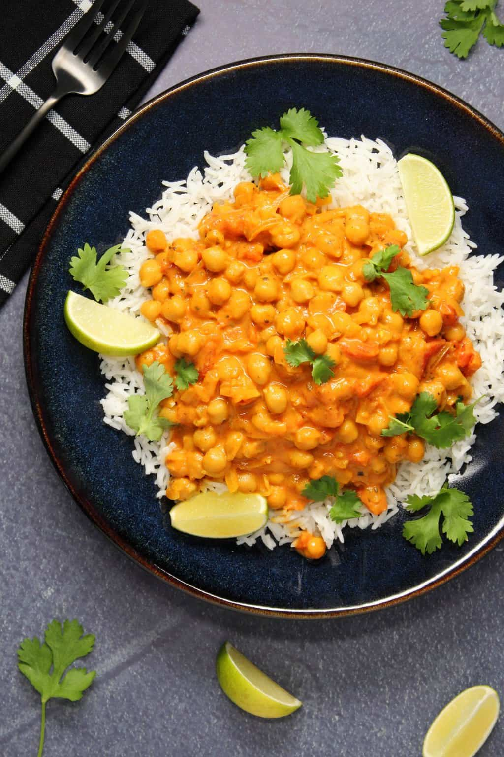Vegan chickpea curry with basmati rice, fresh cilantro and fresh lime in a black bowl.