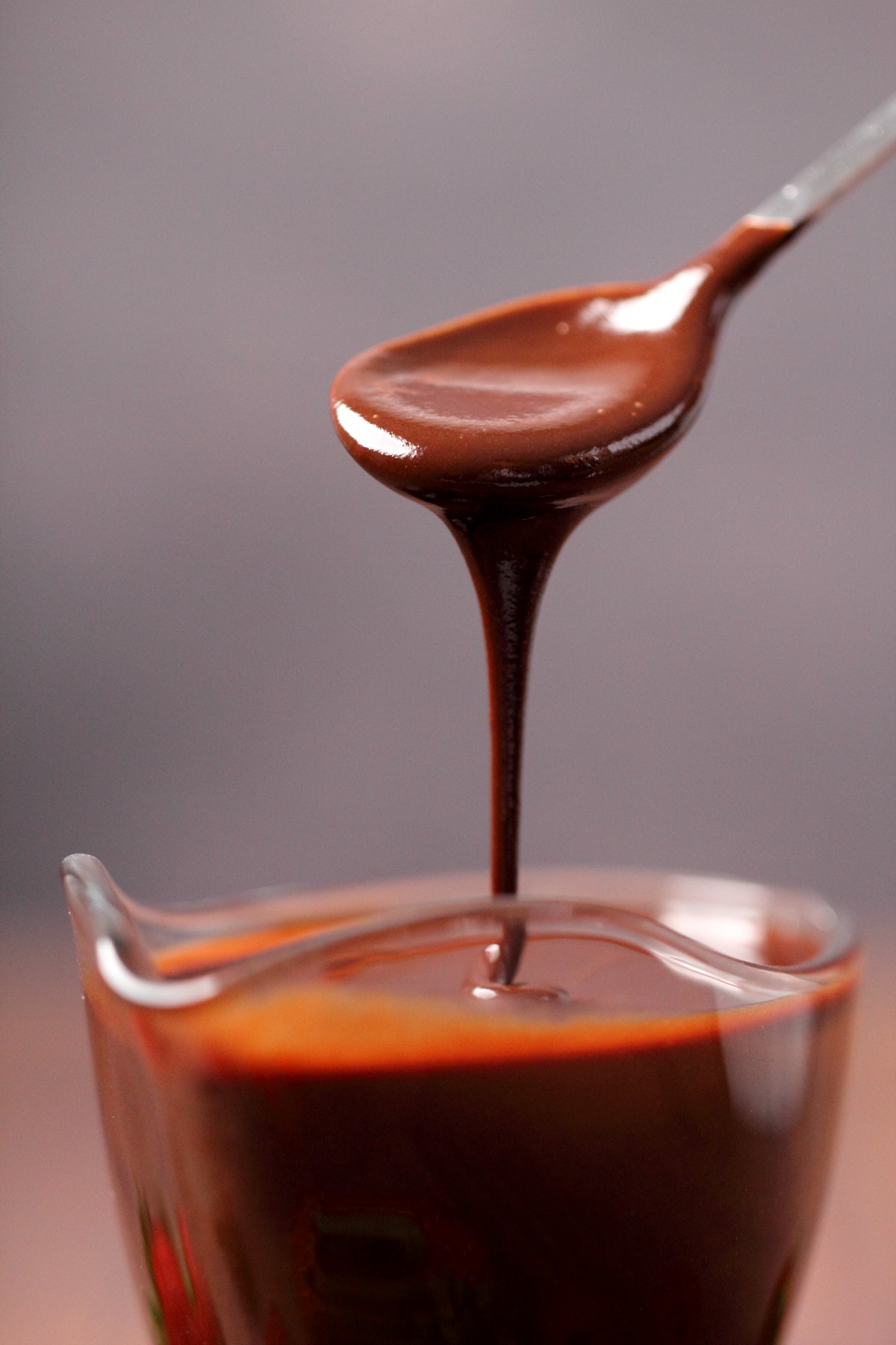 Vegan chocolate sauce pouring off a spoon.