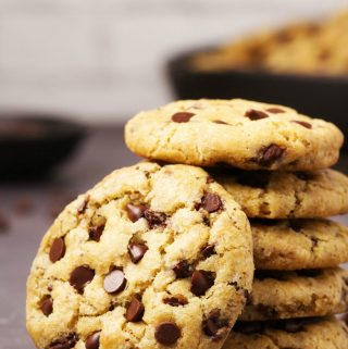 Vegan gluten free chocolate chip cookie leaning against a stack of cookies.