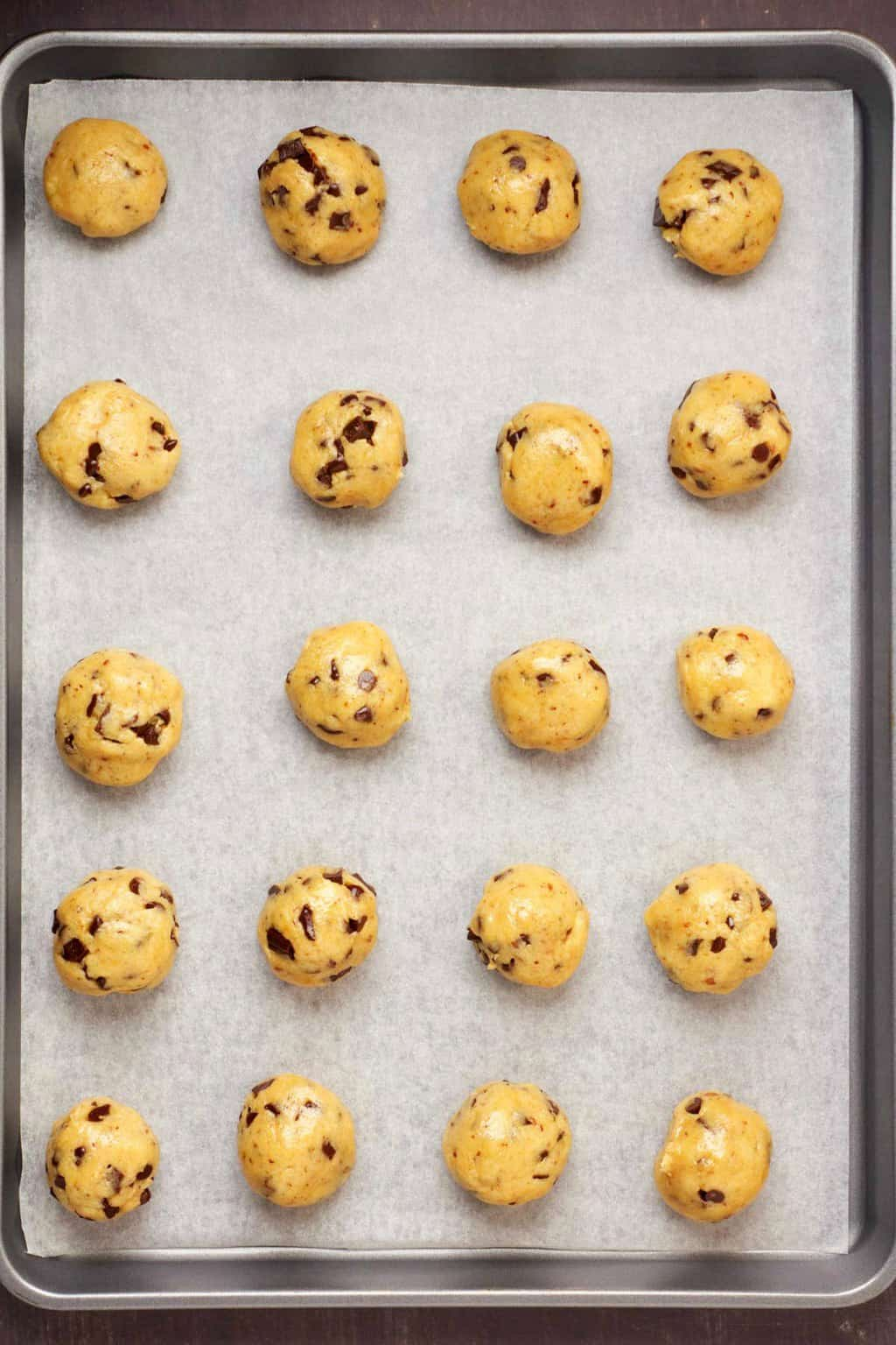 Vegan gluten free chocolate chip cookie dough rolled into balls on a parchment lined baking sheet.
