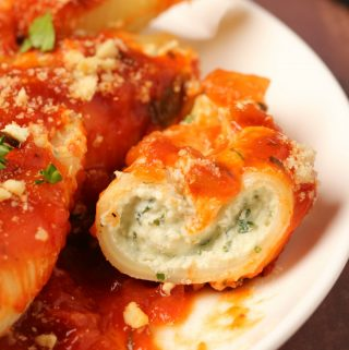 Vegan stuffed shells on a white plate with a fork.