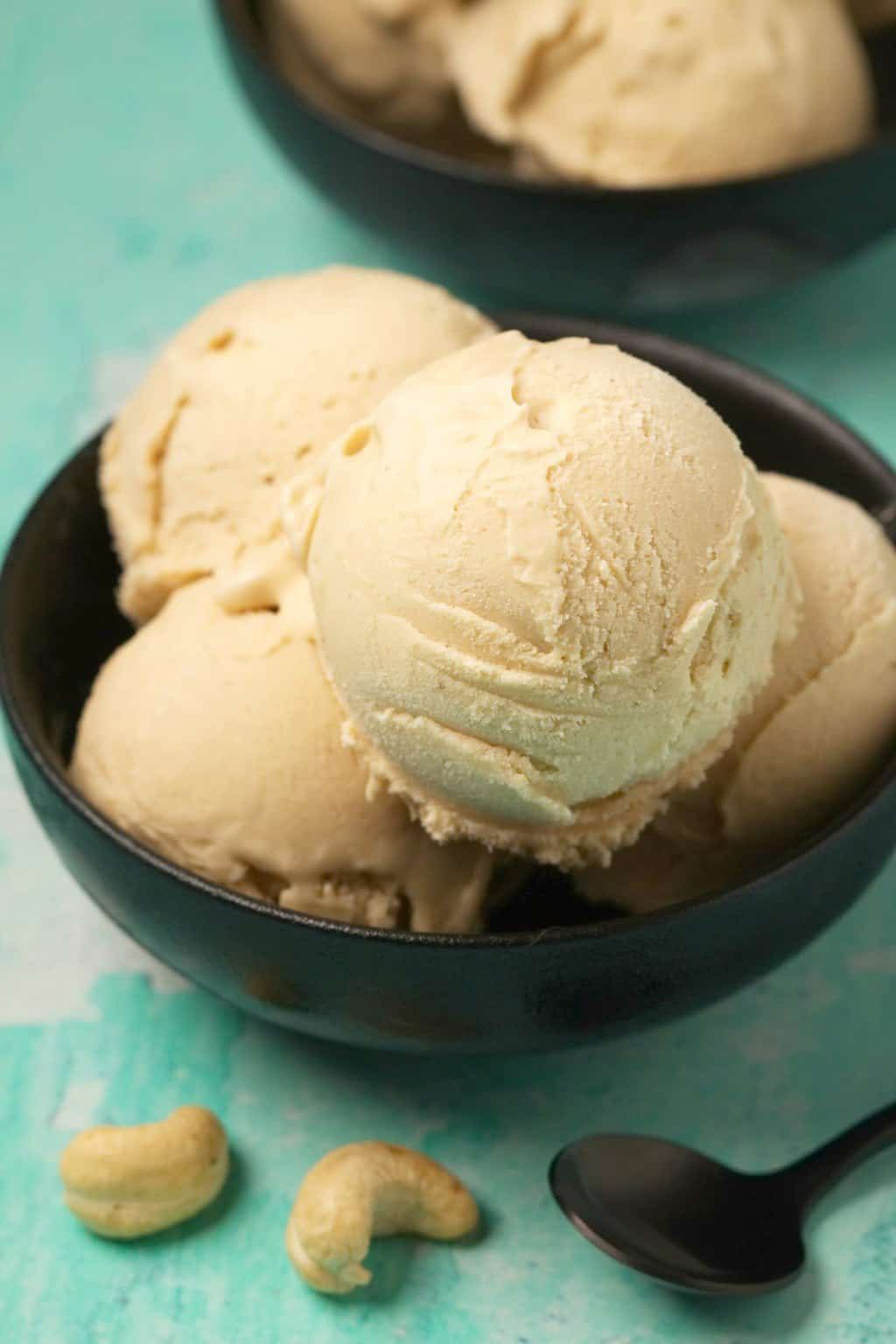 Cashew ice cream scoops in a black bowl with a spoon.