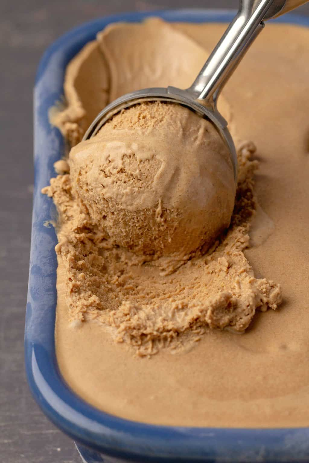 Vegan coffee ice cream in a blue ceramic dish with an ice cream scoop.