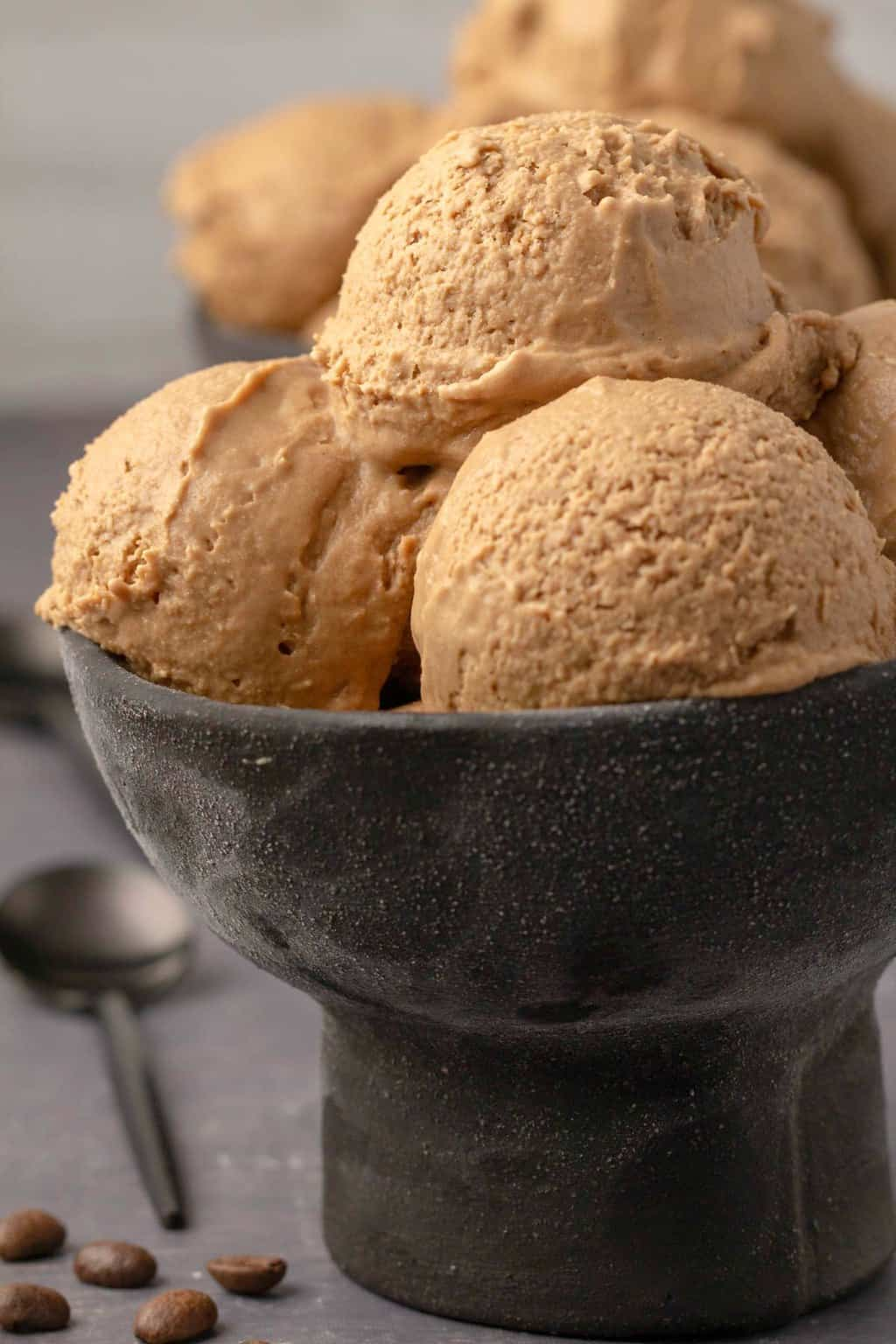 Scoops of vegan coffee ice cream in a black bowl.