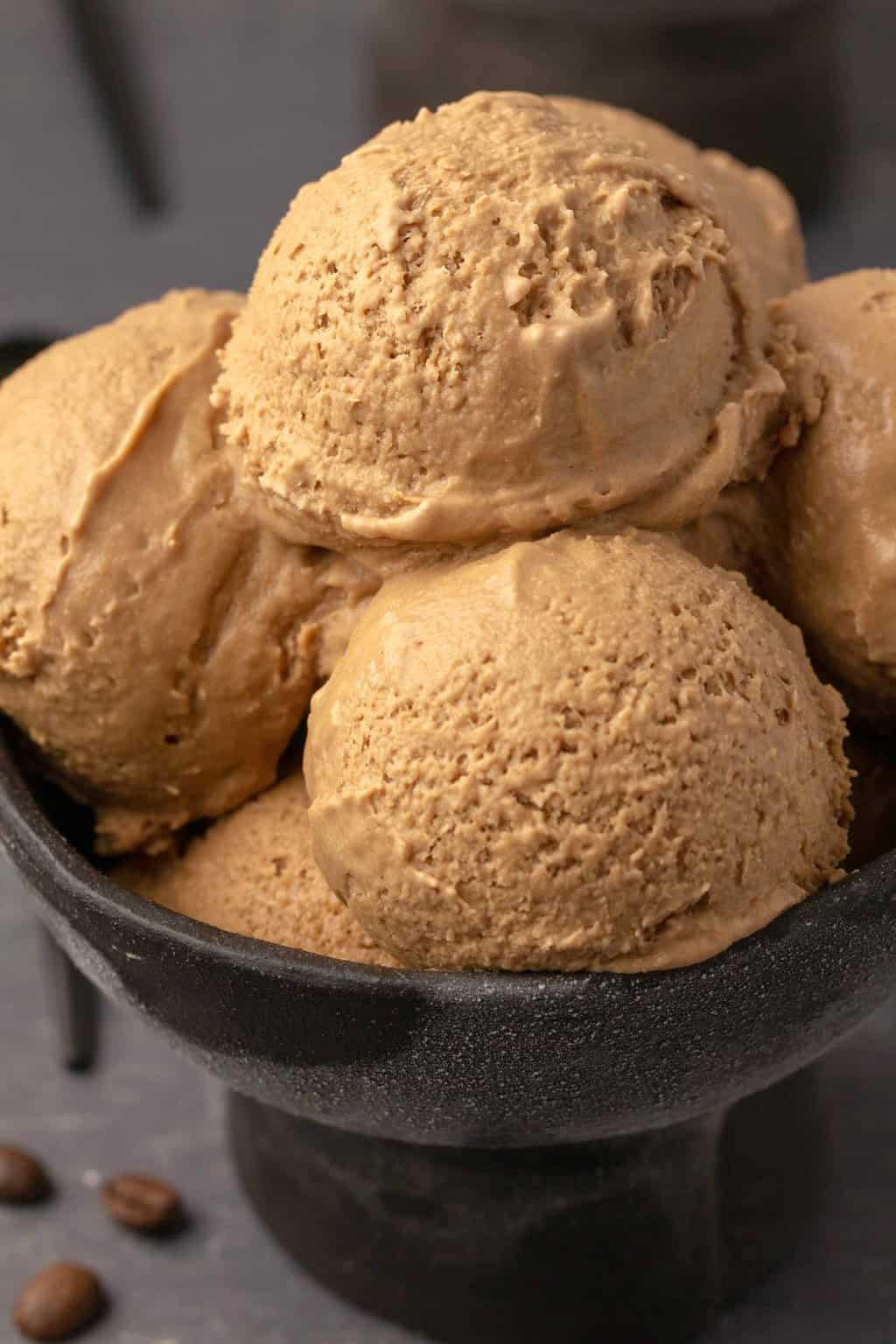 Vegan coffee ice cream scoops in a black bowl.