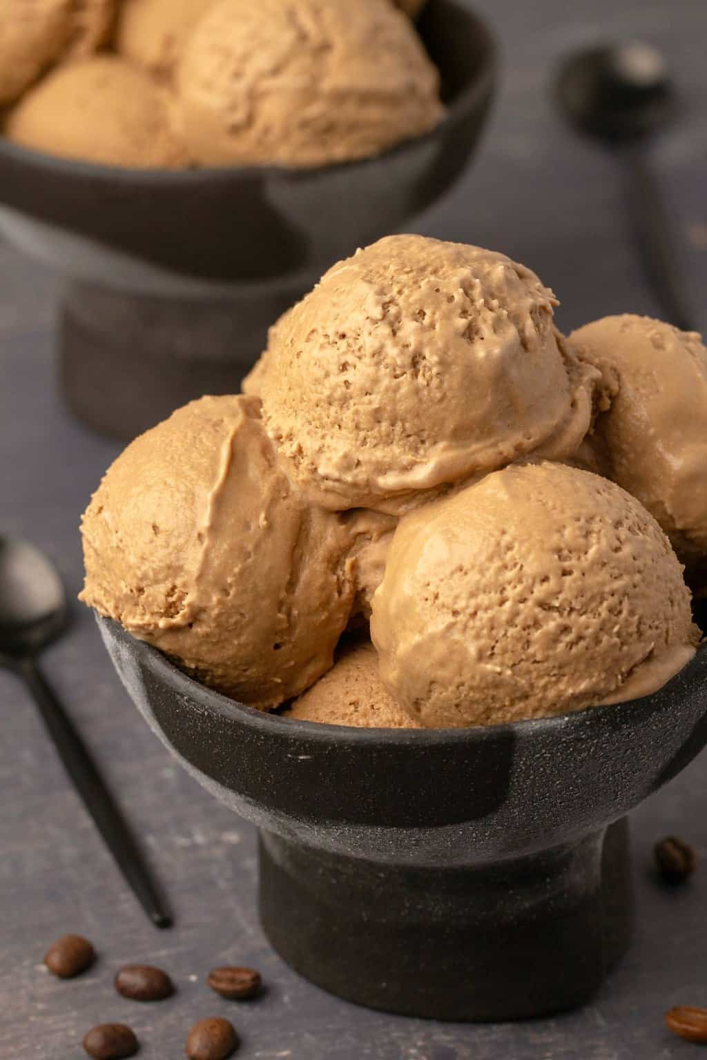 Scoops of vegan coffee ice cream in black bowls.