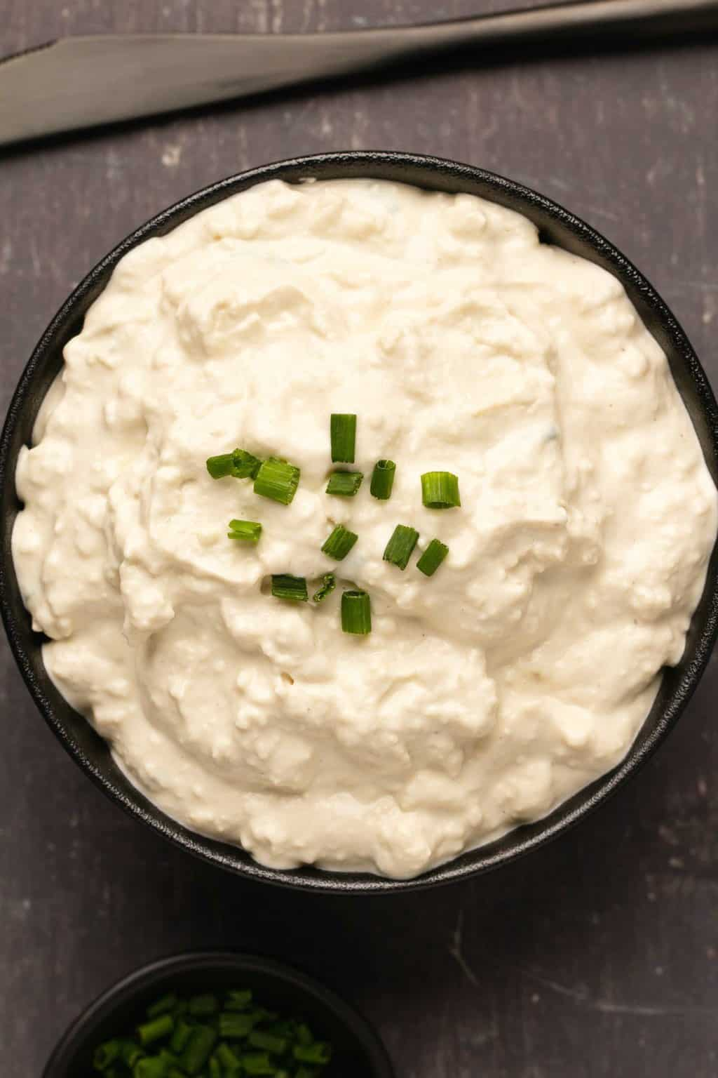 Vegan cottage cheese topped with chopped chives in a black bowl.