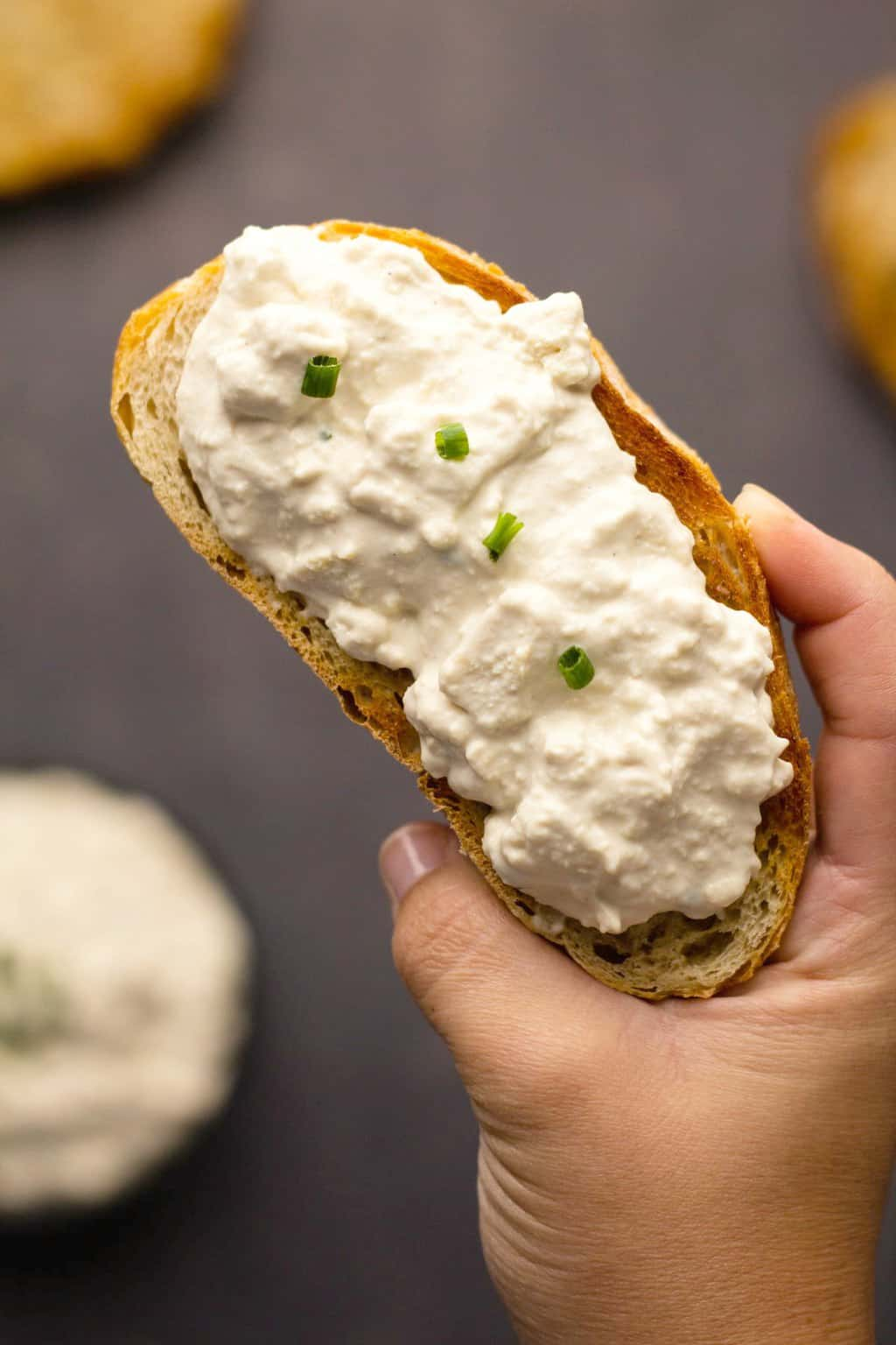 Vegan cottage cheese spread thickly on a slice of toasted ciabatta.