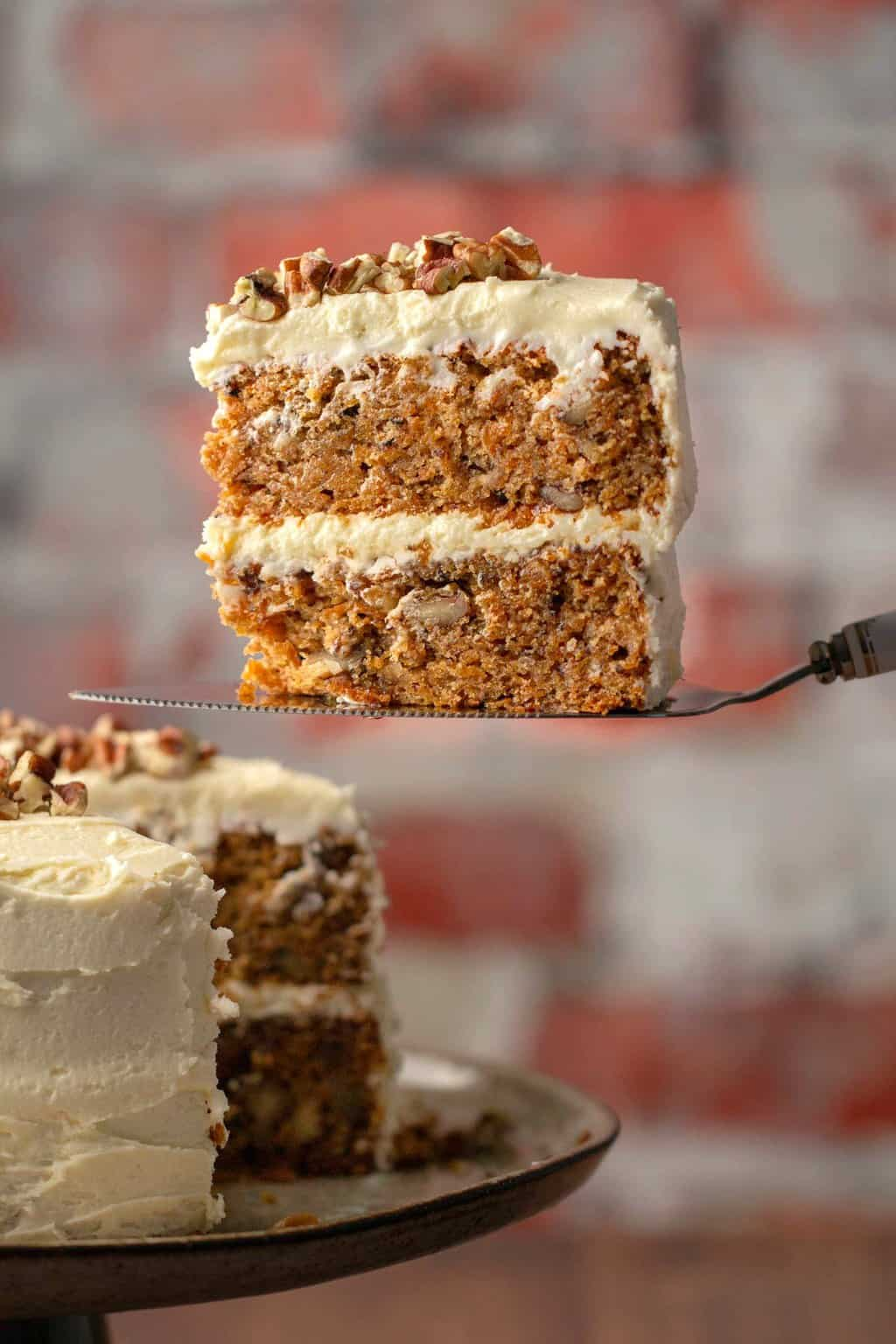 Vegan gluten free carrot cake slice on a cake lifter.