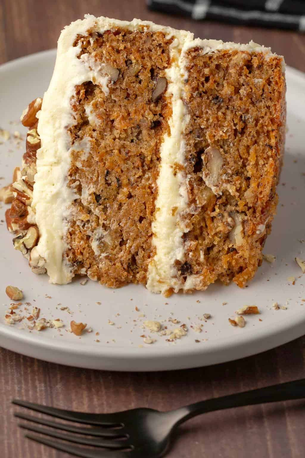 Slice of vegan gluten free carrot cake on a white plate.