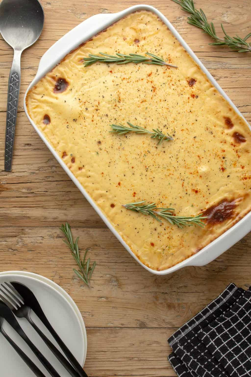 Vegan moussaka topped with fresh rosemary in a white baking dish.