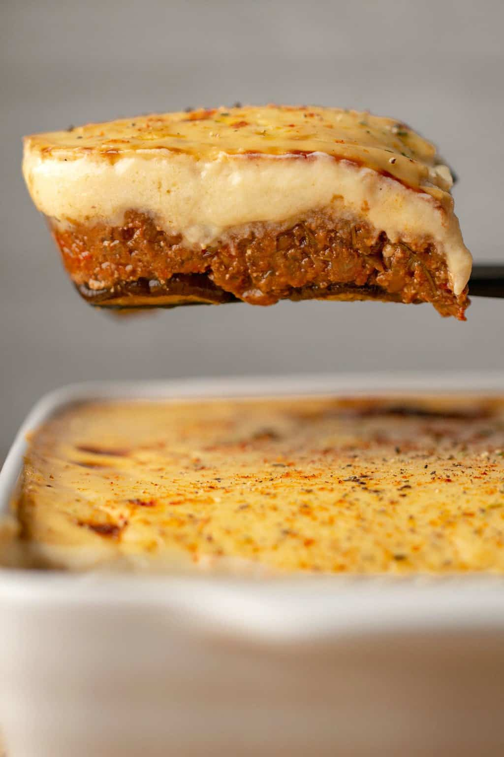 A slice of vegan moussaka on a spatula.